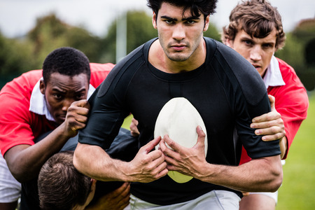 clash: Rugby players tackling during game at the park Stock Photo