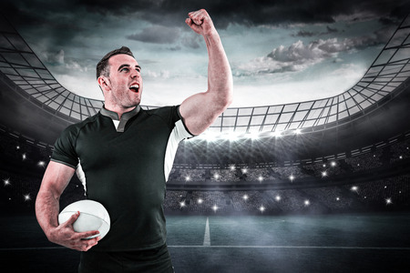 winner man: Rugby player cheering with the ball against large football stadium under blue sky