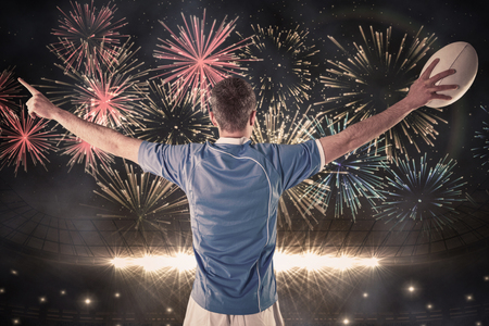 rugby ball: Rugby player about to throw a rugby ball against fireworks exploding over football stadium Stock Photo