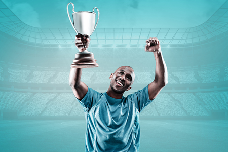 sportsmen: Happy sportsman looking up and cheering while holding trophy against blue vignette background