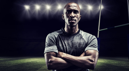 arms crossed: Portrait of confident rugby player with arms crossed against rugby stadium