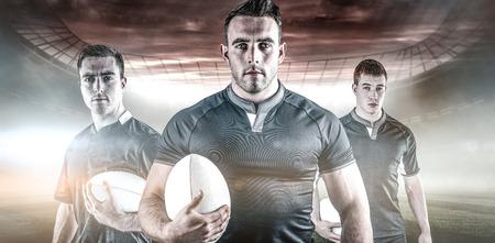 and rugby ball: El jugador de rugby sosteniendo una pelota de rugby contra el campo de rugby