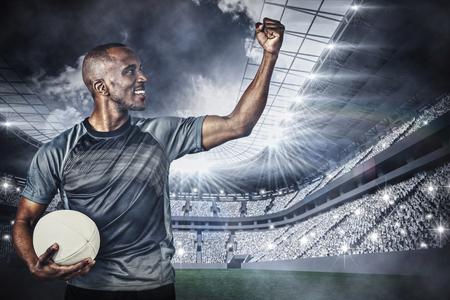 pelota rugby: Deportista con puño sosteniendo pelota de rugby después de la victoria contra el estadio de fútbol con los fans en blanco