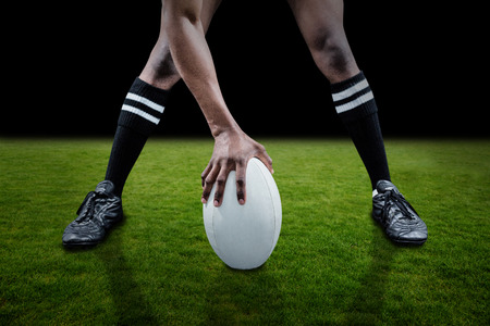 rugby ball: Low section of sportsman playing rugby against green field Stock Photo