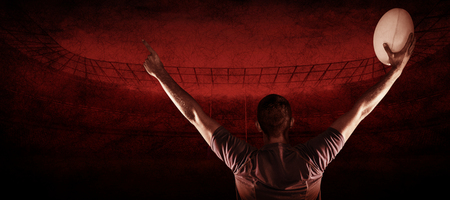 winning pitch: Rear view of rugby player holding ball with arms raised against rugby stadium