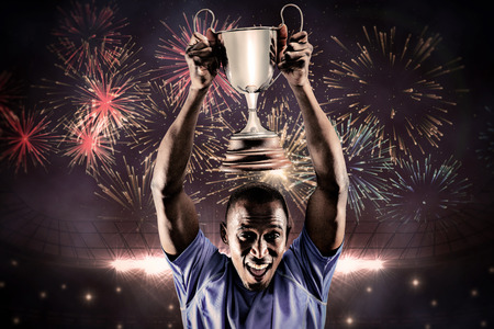 sport celebration: Portrait of happy athlete cheering while holding trophy against fireworks exploding over football stadium Stock Photo