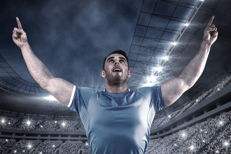 cheering crowd: Rugby player cheering and pointing against football stadium