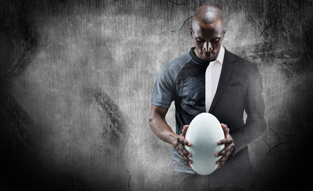 half dressed: Thoughtful athlete looking at rugby ball against half a suit