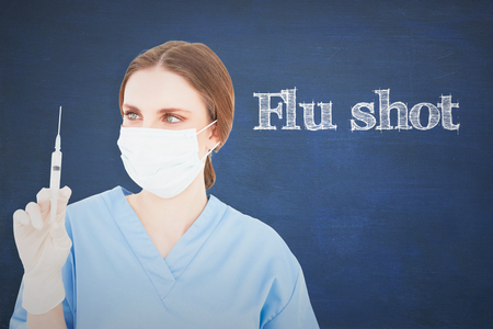 The word flu shot and pretty brunette female doctor holding a syringe and looking at it against chalkboard Stock Photo