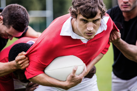 Rugby players tackling during game at the park Banco de Imagens
