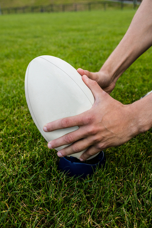 picking up: Rugby player picking up ball at the park