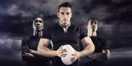 rugby: Tough rugby player looking at camera against blue sky Stock Photo