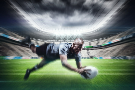 rugby ball: Sportsman jumping for catching rugby ball against rugby stadium