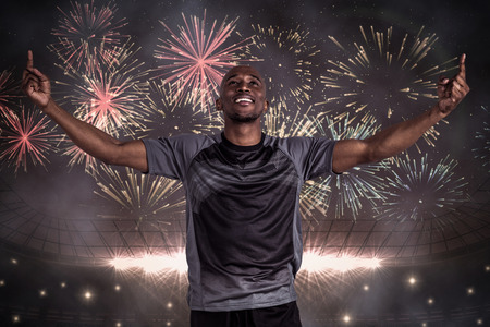celebration event: Happy sportsman with arms raised after victory against fireworks exploding over football stadium