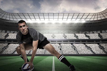 ball stretching: Sports player in black jersey stretching with ball against rugby arena