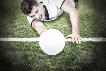 man lying down: Man lying down while holding ball against rugby pitch