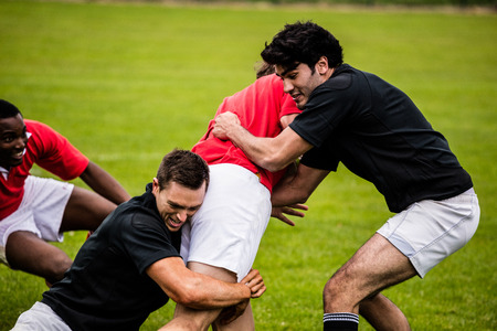 Rugby players tackling during game at the park 스톡 콘텐츠