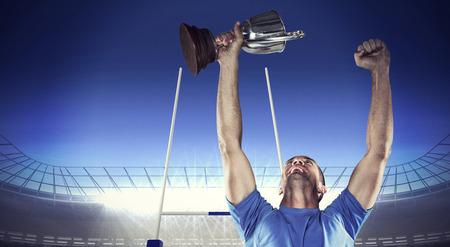trofeo: Jugador de rugby feliz celebración trofeo contra el estadio de rugby Foto de archivo