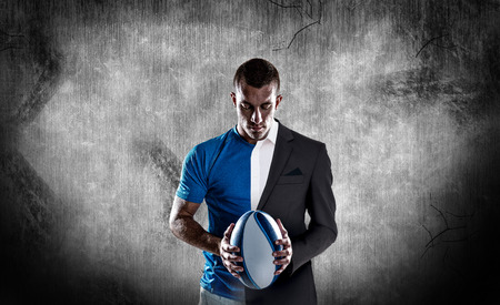 half dressed: Rugby player holding ball against half a suit