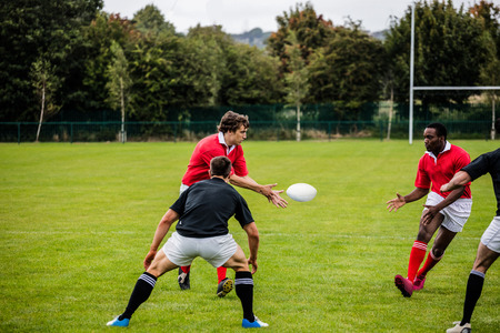 pelota rugby: Jugadores de rugby que pasan durante el juego en el parque