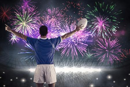 pelota rugby: El jugador de rugby a punto de lanzar una pelota de rugby contra la explosi�n de fuegos artificiales sobre el estadio de f�tbol Foto de archivo