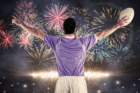 turned out: Rugby player gesturing with hands against fireworks exploding over football stadium Stock Photo