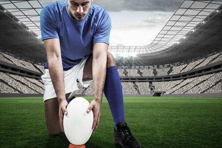 football world cup: Full length of rugby player placing ball against sports stadium