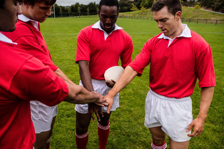 teammates: Rugby players putting hands together at the park