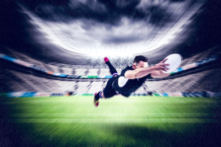 scoring: Rugby player scoring a try against rugby stadium