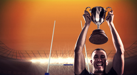 Portrait of successful rugby player holding trophy against rugby stadium