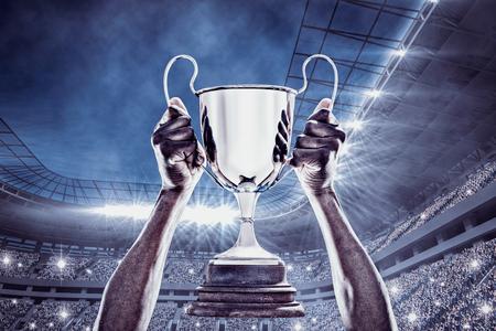 deportista: Mano cosechada de atleta sosteniendo el trofeo contra el estadio de fútbol
