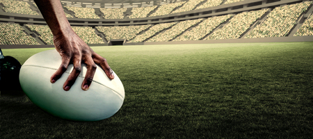 rugby ball: Cropped image of athlete holding rugby ball against rugby stadium