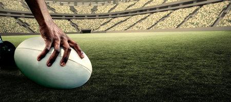 pelota rugby: Imagen recortada de atleta sosteniendo pelota de rugby contra el estadio de rugby