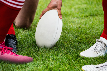 teammates: Rugby players in huddle with ball at the park Stock Photo