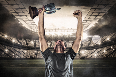 Happy rugby player holding trophy against large football stadium with lights