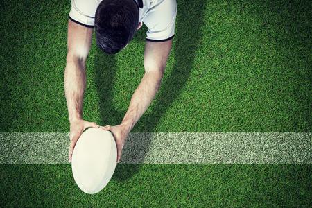 pelota rugby: Vista de ángulo alto de hombre con pelota de rugby con ambas manos contra el terreno de juego con la línea