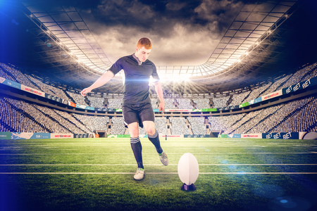 young caucasian: Rugby player doing a drop kick against rugby stadium