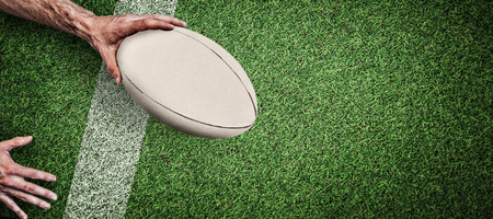 Cropped image of a man holding rugby ball against pitch with line Foto de archivo