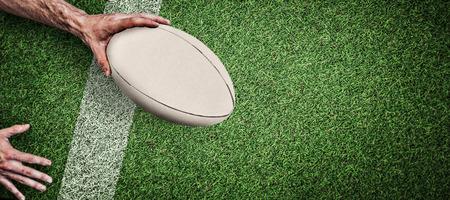 pelota rugby: Recorta la imagen de una pelota de rugby hombre que sostiene contra el terreno de juego con la línea