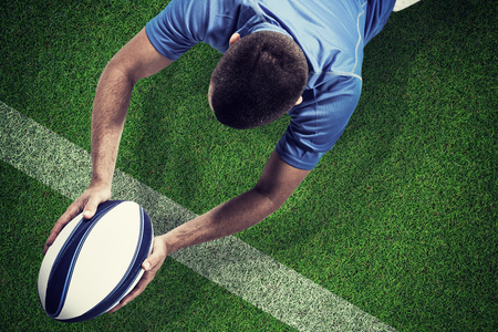 player: Rugby player lying in front with ball against pitch with line