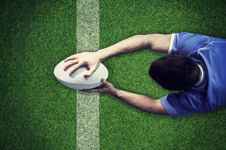 scoring: A rugby player scoring a try against pitch with line
