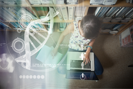 Illustration of DNA against student using laptop against bookshelf on the library floor