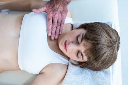 reiki: High angle view of male therapist performing reiki over woman at health club