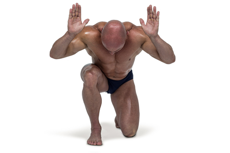 knee bend: Muscular man bending on knee with arms raised against white background Stock Photo