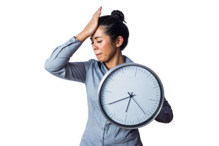 time flies: Woman slapping her forehead and holding a clock against a white background Stock Photo