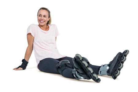inline skater: Happy female inline skater relaxing over white background