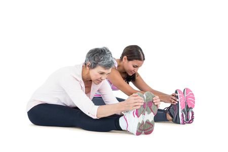 touching toes: Women sitting and exercising on white background