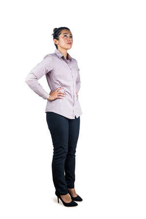 looking upwards: Businesswoman looking upwards with hands on hips against a white background Stock Photo