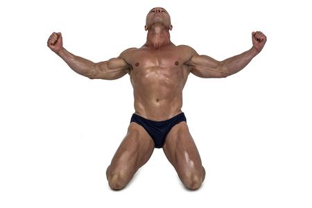 hombre fuerte: Muscular hombre arrodillado con los brazos extendidos contra el fondo blanco Foto de archivo