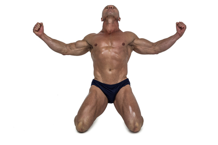 macho man: Muscular man kneeling down with arms outstretched against white background